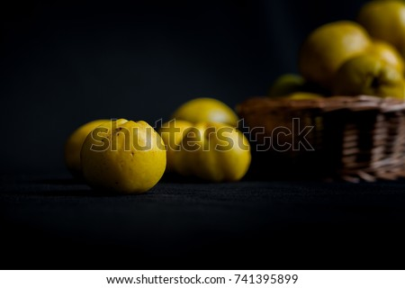 Ripped yellow fruits of quince (Chaenomeles) on dark background table and in woven basket in muted day light. Close up detailed shot with selective focus and shallow depth of field