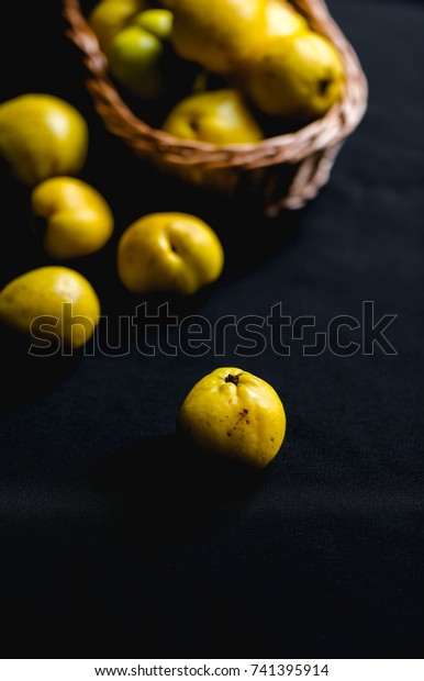 Ripped yellow fruits of quince (Chaenomeles) on dark background table and in woven basket in muted daylight.