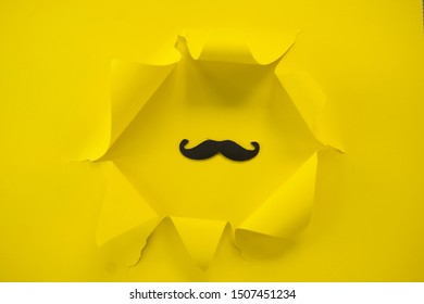 ripped yellow paper against a yellow background with mustache in it.