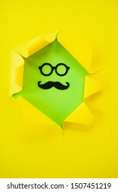 ripped yellow paper against a green background with mustache and glass in it.