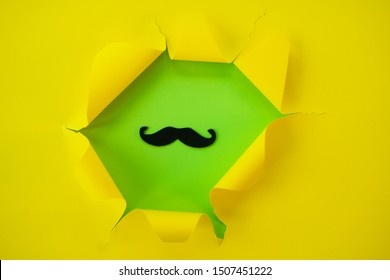 ripped yellow paper against a green background with mustache in it