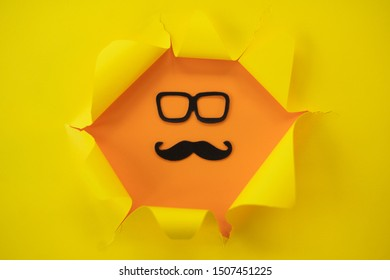 ripped yellow paper against a orange background with mustache and glass in it.