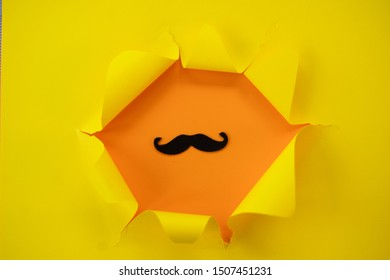 ripped yellow paper against a orange background with mustache in it.