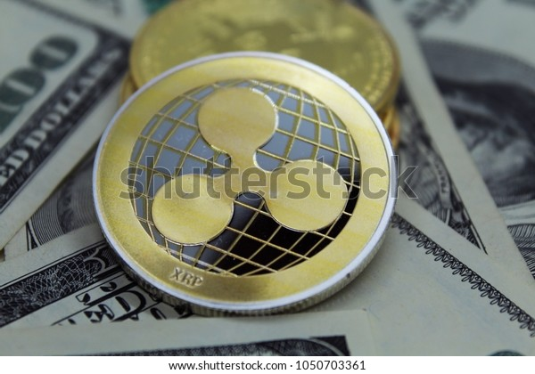 Ripple Coin and banknotes.Ripple crypto-currency on dollar notes.