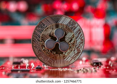 Ripple coin on intergrated circuit and red blurry background representing plumeting market price