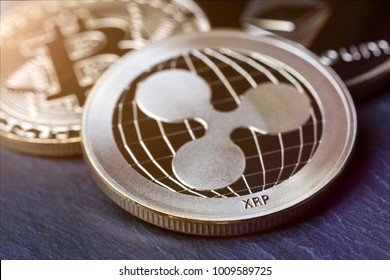 ripple coin and other crypto coins on a slate plate