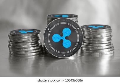 Ripple crypto currency (XRP) closeup. Stack of black and silver coins. Cyber money.