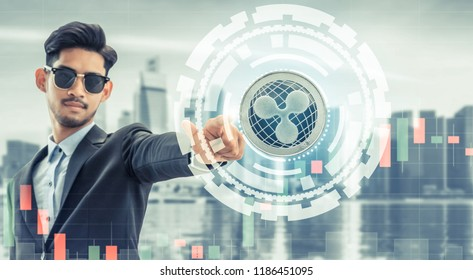 Ripple and cryptocurrency investing concept - Businessman pointing at Ripple (XRP) with modern business building and cityscape in the background. Blockchain technology.