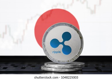 RIPPLE (XRP) cryptocurrency; physical concept ripple coin on the background of the flag of Japan