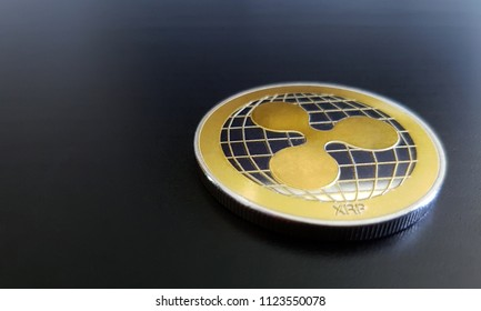 Ripple XRP golden cryptocurrency coin lying on a dark wooden theme background
