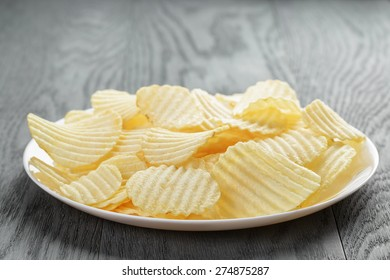 rippled potato chips in white plate on wood table