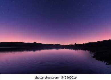 Ripples on a mirror calm lac de Codole in the Balagne region of Corsica at dawn with a pink and purple star filled sky