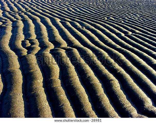 Ripples in sand at beach.
