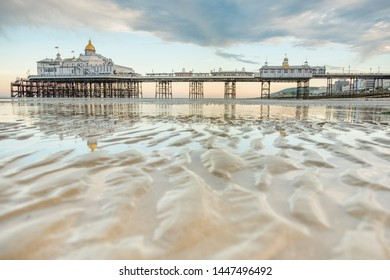 Ripples in the sand and Eastbourne Pier at low tide
