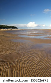 Ripples in the sand at low tide at Wells next the sea in north Norfolk UK with the pine trees, beach huts and sea cloud on the horizon.  A blue sky in autumn on the north coast.