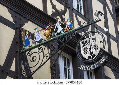 RIQUEWIHR, FRANCE - FEBRUARY 23, 2017:  The sign above the entrance to wine producer Hugel et Fils on the corner of the main high street, Rue du General de Gaulle, and Rue de la 1E Armée.