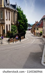 Riquewihr, France - July 19, 2017:  Couple walks down empty street in a small village in the Alsace wine region in France.