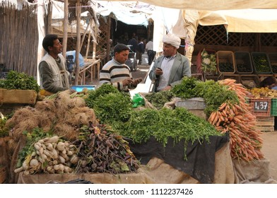 Risani, Morocco - march 20, 2012: Shopkeepers and farmers trying prices at a vegetable stand in the rural market of the city