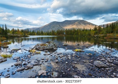 Rischorr mountain reflection in shallow Polygonal northern taiga forest lake with small rocks on foreground, Hibiny mountains above the Arctic Circle, Russia
