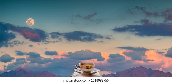 Rise of Super-moon above mountains. On foreground is a cup of coffee with saucer placed on a wooden plate. collage of three images