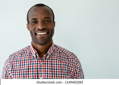 Rised mood. Cheerful handsome afro american man smiling against white background
