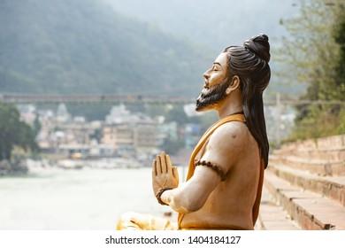 RISHIKESH - INDIA - 18 MAY 2019. Stunning view of a sitting Hindu statue on the riverbank of the Ganges river. Blurred Lakshman Jhula bridge in the background. Rishikesh, Uttarakhand, India.
