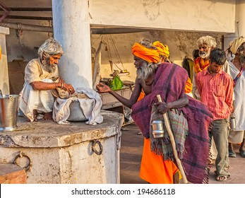 RISHIKESH, INDIA - APRIL 5, 2010: The man sharing the food free of charge to the devotees who are standing in line dressed in orange clothing.