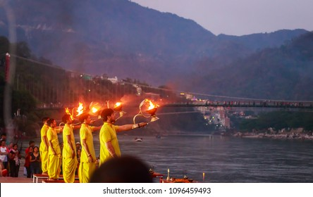 Rishikesh, India, May 20,2018: Young priests perform the holy Ganga aarti ceremony rituals with holy fire at dawn at the Ganges river bank at Rishikesh Ram Jhula, India.