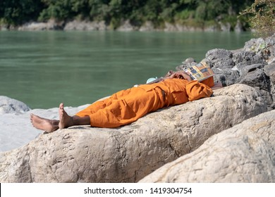 RISHIKESH, INDIA - NOVEMBER 06, 2018 : Hindu sadhu holy man, sleeps on the shore covered his head with a newspaper on a sunny day near the Ganges river water in Rishikesh, India, close up