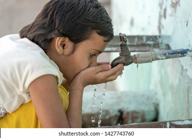 RISHIKESH, INDIA - NOVEMBER 06, 2018 : Portrait of thirsty Indian girl drinks water from the outdoor tap on the street in Rishikesh, India