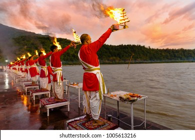 Rishikesh, Uttarakhand - August 03 2016: Priests in red robe in the holy city of Rishikesh in Uttarakhand, India during the evening light ceremony called Ganga arthi to worship river Ganga / Ganges.