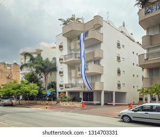 Rishon LeTsiyon, Israel-April 18, 2013: State flag of Israel hangs along of the 4 stories newly built residential house. There is a tradition to hang the national flag on independence day.