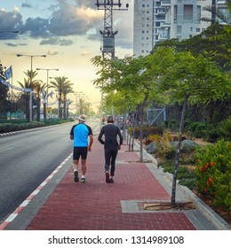 Rishon LeTsiyon, Israel-April 25, 2013: Two retired men keep themselves fit jogging on the sidewalk along the driving way in the evening time.