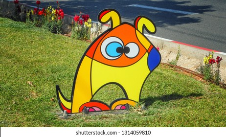 Rishon LeTsiyon, Israel-April 26, 2013: A multi-colored painted metal sculpture of funny dog sets on grass lawn along the sidewalk.