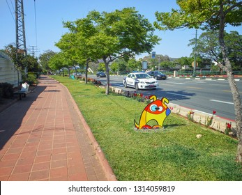 Rishon LeTsiyon, Israel-April 26, 2013: The sidewalk along the highway has a separation grass lawn with a piece of street sculpture depicting a sitting dog made of metal and painted in bright colors.