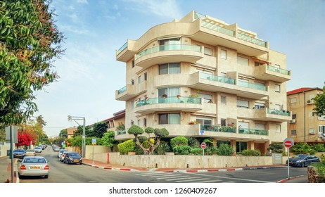 Rishon LeTsiyon, Israel-April 3, 2018: Bauhaus style new residence building with yellow tiled facade stands at the corner of the street. The open balconies extend off the facade.