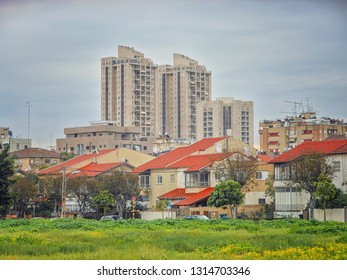 Rishon LeTsiyon, Israel-January 11, 2013: Modern city combines as old one-two story renovated townhouses with red sloped roofs at front view and tall residential towers at the background.