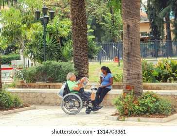 Rishon LeTsiyon, Israel-July 14, 2013: A nurse and a disabled man in the wheelchair are in the city park. The caregiver chats on the mobile phone and the old man read a newspaper.