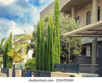 Rishon LeTsiyon, Israel-July 17, 2013: Private family townhouse with conical green thujas in the courtyard behind the walls with steel grey gates.