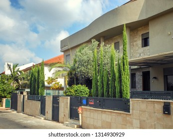 Rishon LeTsiyon, Israel-July 17, 2013: Two family townhouse comprises 2 floors and two columns in the central part of the facade that is faced with Jerusalem stone tiles. Their courtyards have thujas