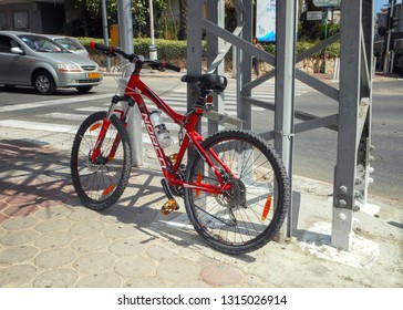 Rishon LeTsiyon, Israel-July 2, 2013: Red bicycle is shackled to the metal electric pole on a sidewalk. Bright sunny day.