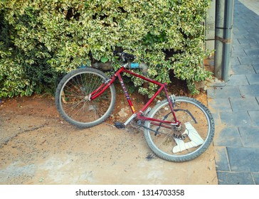 Rishon LeTsiyon, Israel-July 5, 2013: A simple red bicycle lies on the ground shackled to the water pipe.