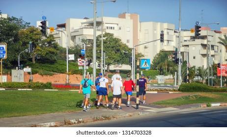 Rishon LeTsiyon, Israel-June 1, 2013: Morning hike of a group of old men along the road sidewalk.