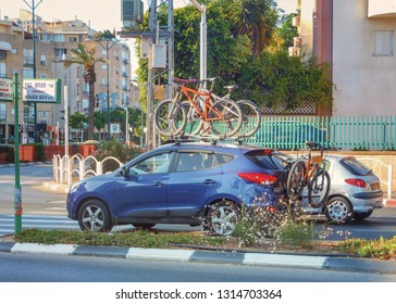 Rishon LeTsiyon, Israel-June 15, 2013: A blue sedan carries two mountain bikes on the roof and one bike on the boot.