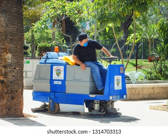 Rishon LeTsiyon, Israel-June 2, 2013: Special machine sweeps and cleans the walking lanes in the city park. The operator a middle-aged man dressed in uniform drives the sweeper.
