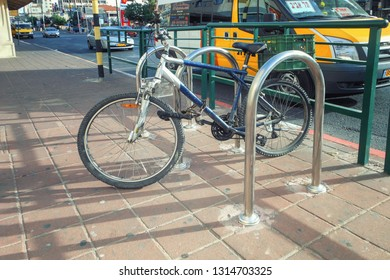 Rishon LeTsiyon, Israel-June 8, 2013: Special bicycle parking place at the rim of the sidewalk. One bike is shackled to a stainless steel bow.