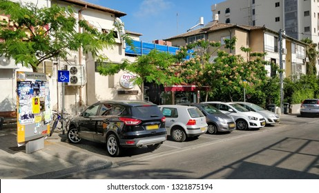 Rishon LeTsiyon, Israel-June 9, 2018: Public parking in the Hatikva street. Special park for disabled has special traffic sign. A bulletin advertising board is on the pavement.
