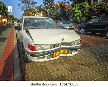 Rishon LeTsiyon, Israel-March 15, 2013: White sedan car ran into a pole smashing collision bumper and the hood. The driver did not fast the belt and hit the head over and cracked the windscreen.