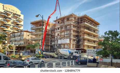 Rishon LeTsiyon, Israel-March 22, 2018: Old residential building in scaffolding and form-work. The process of casting concrete for building up stories by means of pumping concrete with a special pump.
