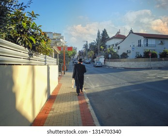 Rishon LeTsiyon, Israel-March 28, 2013: The lonely middle-aged orthodox Jew in a black hat and black overcoat walks along the sidewalk of empty evening street.